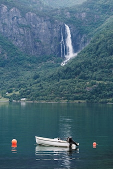 Weißes boot in einem norwegischen fjord. blick auf den wasserfall feigumfossen. lusterfjord, gemeinde luster, norwegen. allein mit der natur