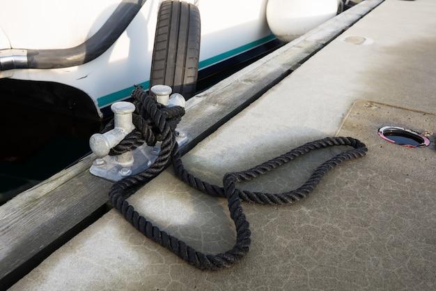 Weißes boot mit einem schwarzen seil an den pier gebunden