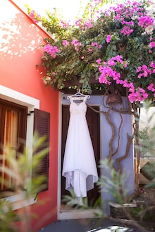 Weißes brautjungfernkleid, das an den aufhängern mit einer aufschrift in der russischen braut unter dem blühenden bouganvilla in einem ruhigen hof auf santorini, griechenland hängt