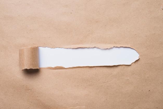 Weißes brett, das durch kraftpapier schaut