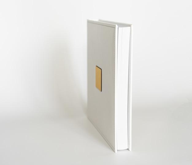 Weißes buch in ledereinband mit goldener metalleinlage zur beschriftung. druckprodukte. fotobücher und alben. einzelne produkte.
