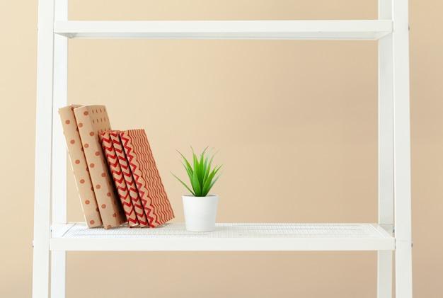 Weißes bücherregal mit büchern und briefpapier gegen beige wand