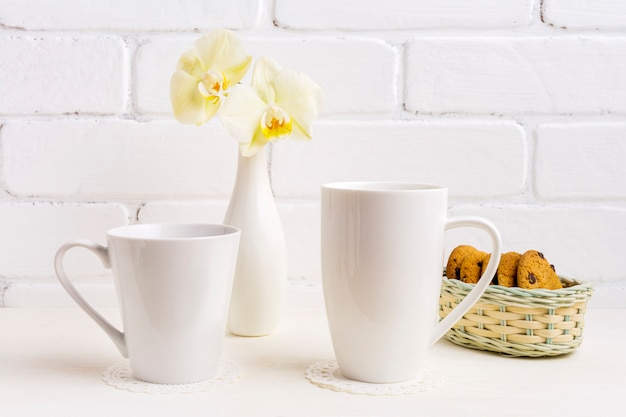 Weißes cappuccino- und kaffee-latte-becher-modell mit gelber orchidee in der vase und in den keksen