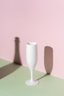 Weißes champagnerglas auf hellem hintergrund.
