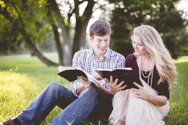 Weißes christliches paar, das das lesen der bibel mitten auf einem feld genießt