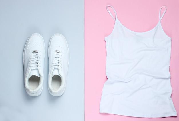 Weißes damen-t-shirt, weiße hipster-turnschuhe auf einem rosa-grauen pastellhintergrund.