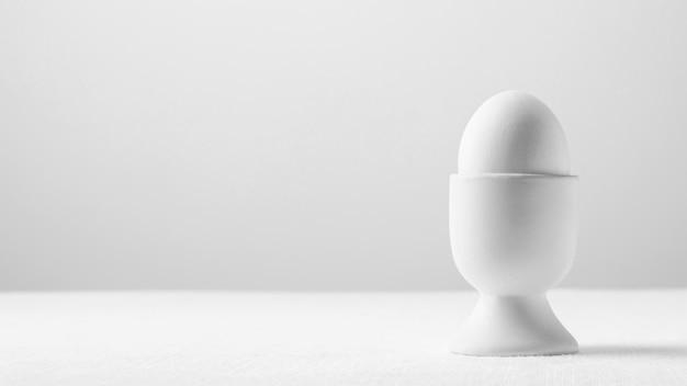 Weißes ei der vorderansicht im ständer mit kopierraum