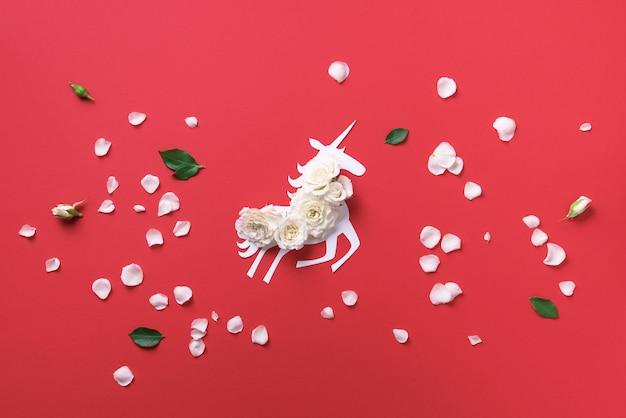 Weißes einhorn mit blumen über korallenrotem papierhintergrund