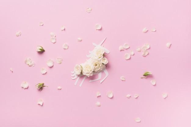 Weißes einhorn mit blumen über rosa papierhintergrund