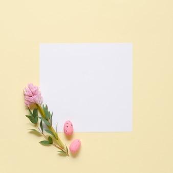 Weißes einladungskartenmodell mit eukalyptuszweigen und rosa ostereiern auf gelbem hintergrund.