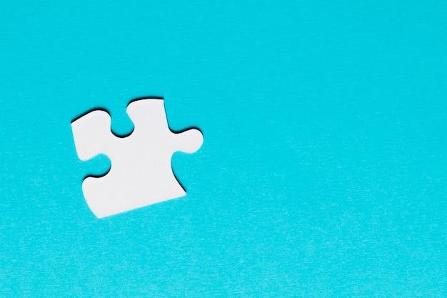Weißes einzelnes puzzlespielstück auf blauem hintergrund