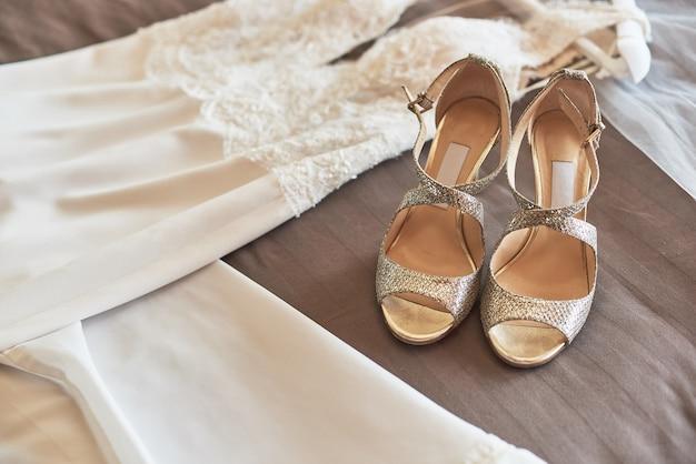 Weißes elegantes hochzeitskleid und schuhe, die auf dem bett liegen.