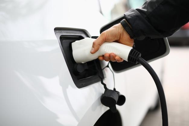 Weißes elektroauto wird an der ladestation aufgeladen.