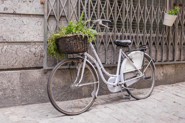 Weißes fahrrad mit weidenkorb