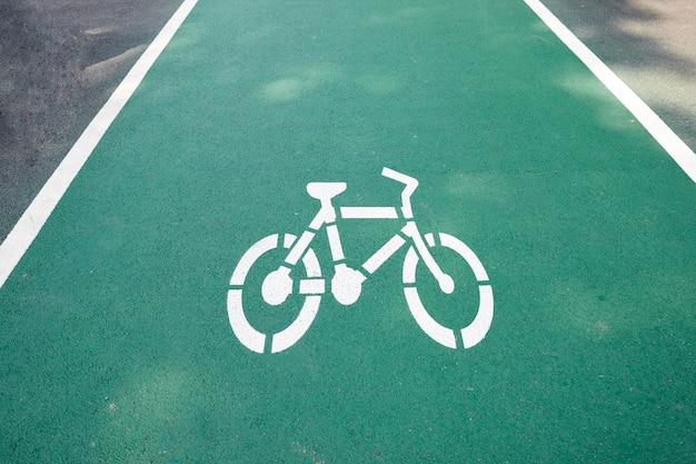Weißes fahrradwegzeichen auf dem grünen weg.
