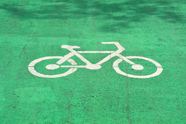 Weißes fahrradzeichen gemalt auf einer grünen asphaltstraße.