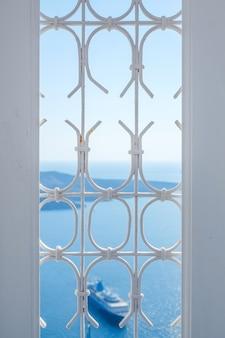 Weißes fenster und schiff in blauem himmel und meer in santorini insel, oia, griechenland