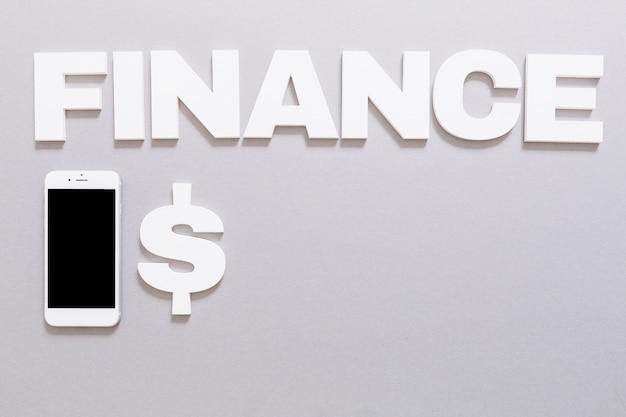 Weißes finanzwort mit dollarzeichen und smartphone auf grauem hintergrund