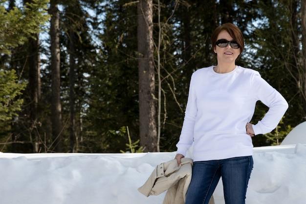 Weißes fleece-rundhalsausschnitt-sweatshirtmodell, das eine frau im winterwald kennzeichnet. schwere sweatshirt vorlage