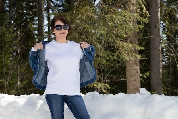 Weißes fleece-sweatshirt-modell mit rundhalsausschnitt, das eine frau trägt, die jeansjacke trägt. schwere sweatshirt vorlage