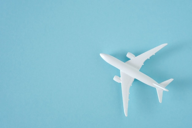 Weißes flugzeug auf draufsicht des blauen hintergrunds