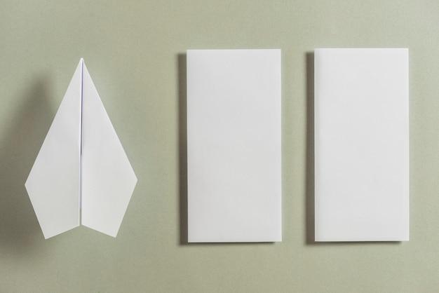 Weißes flugzeug außer zwei faltete papiere auf hellem hintergrund