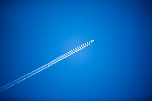 Weißes flugzeug fliegt hoch am blauen himmel