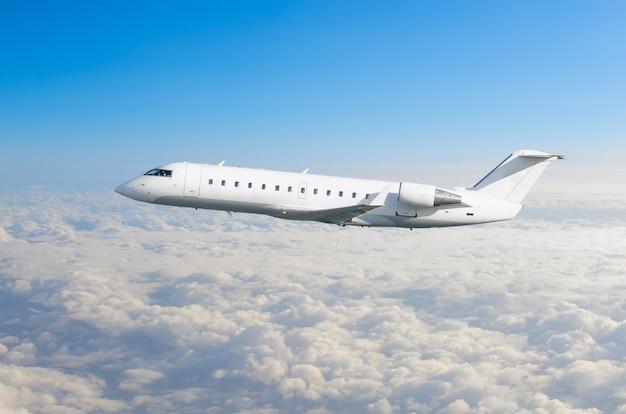 Weißes flugzeug fliegt über den wolken.