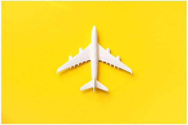Weißes flugzeug, flugzeug auf gelbem farbhintergrund mit kopienraum.