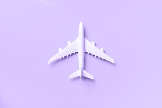Weißes flugzeug, flugzeug auf modischem violettem farbhintergrund mit kopienraum.