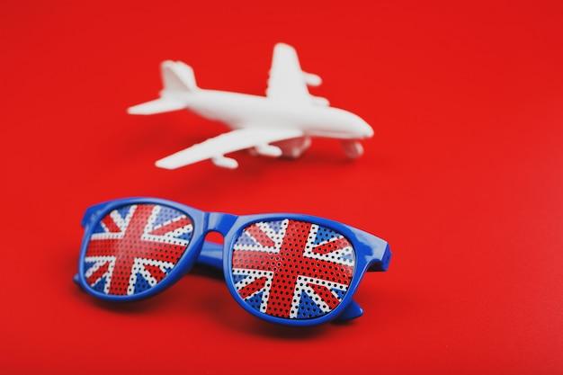 Weißes flugzeug und sonnenbrille mit der flagge des vereinigten königreichs. reise nach england.