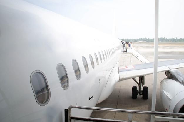 Weißes flugzeug vom kopf beim einsteigen des passagiers