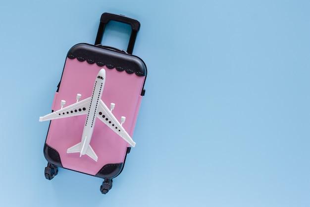 Weißes flugzeugmodell mit rosa koffer auf blau für reise- und reisekonzept