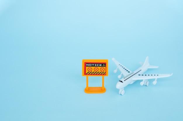 Weißes flugzeugmodell mit verbotszeichen auf blauem hintergrund für fahrzeug und transport im coronavirus- oder covid-2019-situationskonzept