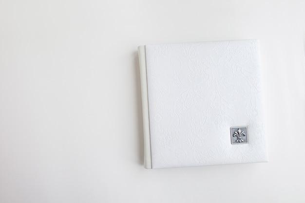 Weißes fotobuch mit lederbezug. stilvolles hochzeitsfotoalbum. familienfotoalbum auf dem weißen tisch. schöner notizblock oder fotobuch mit eleganter durchbrochener prägung auf weißem hintergrund.