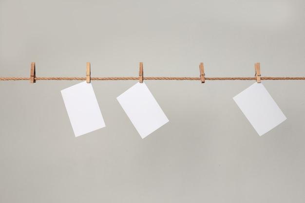 Weißes fotopapier. mit wäscheklammern an einer wäscheleine hängen.