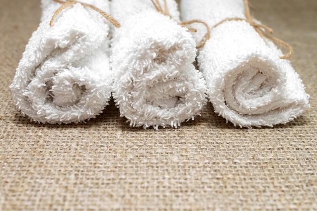 Weißes frottee-baumwolltuch auf leinen-sackleinen gerollt. spa, sauna, konzept für einen gesunden lebensstil. nahansicht. selektiver weichzeichner. . textkopierplatz.