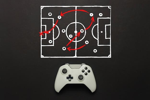 Weißes gamepad auf schwarzem hintergrund. ein fußballfeldschema wurde hinzugefügt. taktik des spiels. konzept-fußballspiel auf der konsole, computerspiele. flache lage, draufsicht.