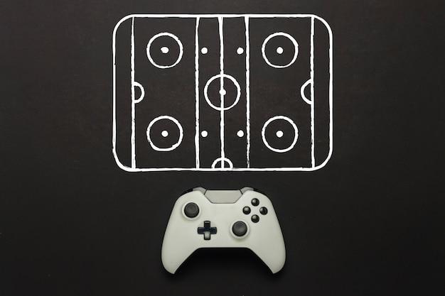 Weißes gamepad auf schwarzem hintergrund. hockeyplatz schema hinzugefügt. konzept hockeyspiel auf der konsole, computerspiele. flache lage, draufsicht.