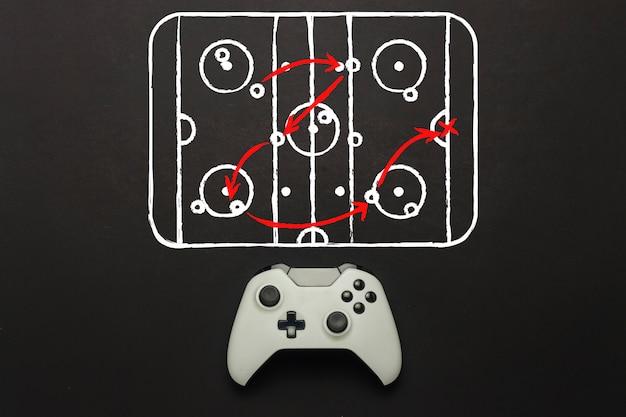 Weißes gamepad auf schwarzem hintergrund. hockeyplatz schema hinzugefügt. taktik des spiels. konzept hockeyspiel auf der konsole, computerspiele. flache lage, draufsicht.