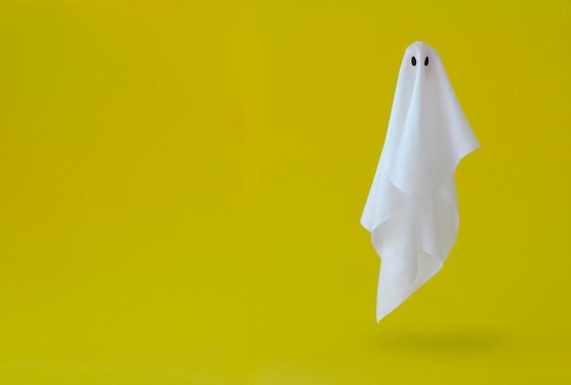 Weißes geistblattkostüm, das in die luft mit gelbem hintergrund fliegt. minimales halloween unheimlich.