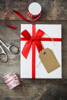 Weißes geschenk mit aufkleber auf holztisch