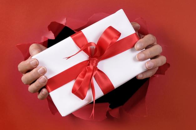 Weißes geschenk mit dem band, das durch einen roten heftigen papierhintergrund geliefert wird.