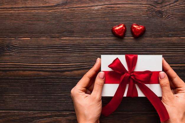 Weißes geschenk mit einem roten band in den händen der frau und zwei schokoladenbonbons in herzform auf einem dunklen hölzernen hintergrund. valentinstag konzept. copyspace.