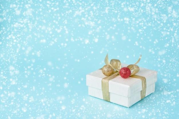 Weißes geschenk oder präsentkarton mit weihnachtsdekoration auf blauem hintergrund, schneebeschaffenheit. .