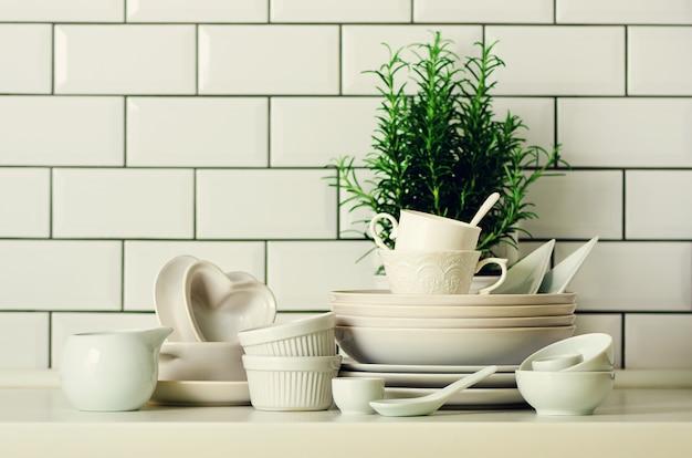 Weißes geschirr zum servieren. geschirr, tassen, löffel, besteck und andere weiße sachen auf dem tisch. küchenzubehör.
