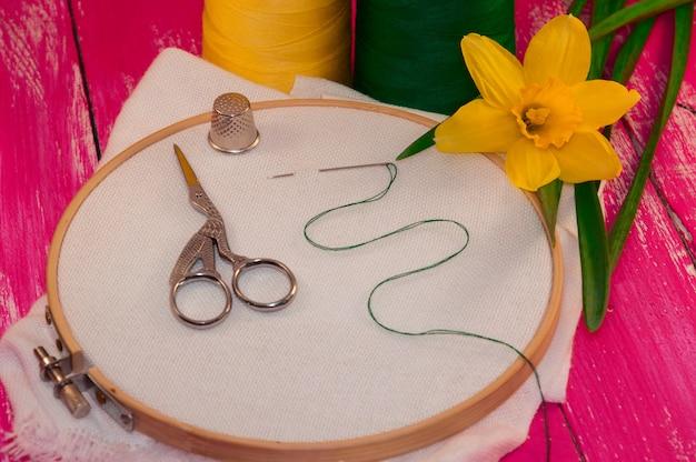 Weißes gewebe im hölzernen stickrahmen für näharbeit auf rosa hölzernem hintergrund