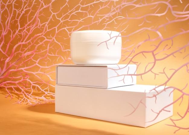 Weißes glas creme auf einem stand mit verzweigter seekoralle. hautpflege am meeresstrand.