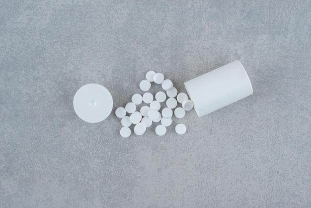 Weißes glas mit medikamenten auf grau