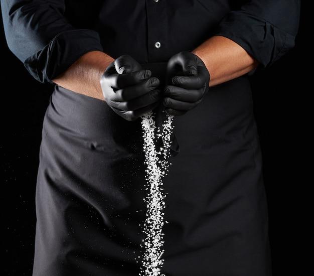 Weißes grobes salz wird aus den handflächen des küchenchefs gegossen, schwarzer raum, ein mann trägt ein schwarzes hemd und eine schürze